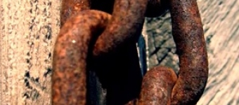 Rusty chain links against timber